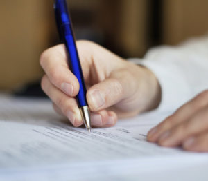 man signing documents with blue pen