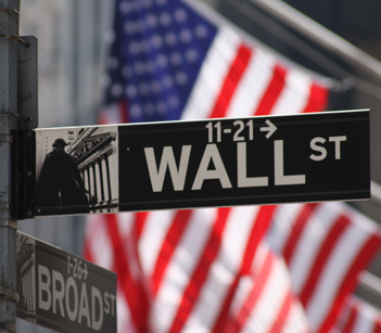Photo of Wall Street, New York City street sign in front of American flags on New York Stock Exchange (NYSE).